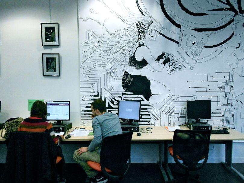 Un bibliothécaire aide une utilisatrice (bibliothèque Louise-Michel, Paris)